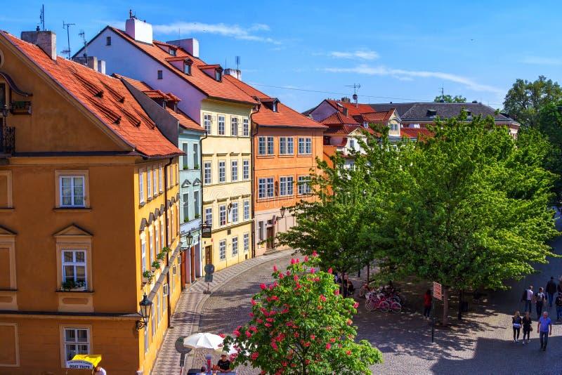 Vårcityscape av Prague med historiska byggnader som går folk, gröna träd och blå himmel fotografering för bildbyråer