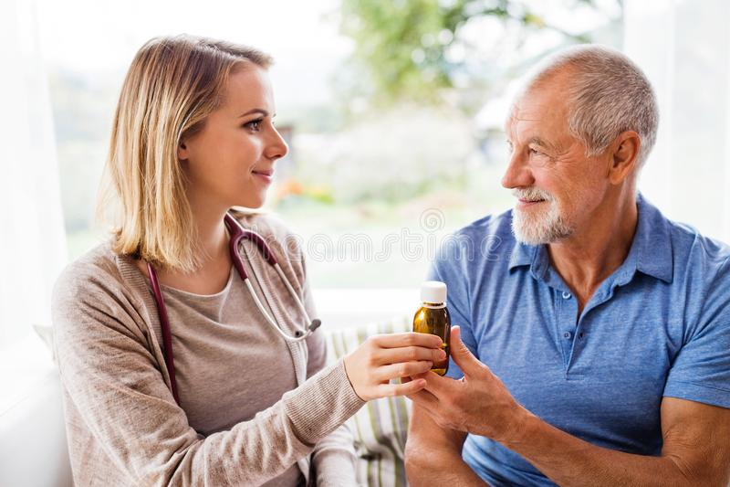 Vård- besökare och en hög man under hem- besök arkivfoton