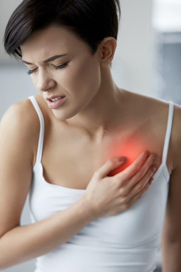 Vård- frågor Den härliga kvinnan som känner sig stark, smärtar i bröstkorg arkivfoto