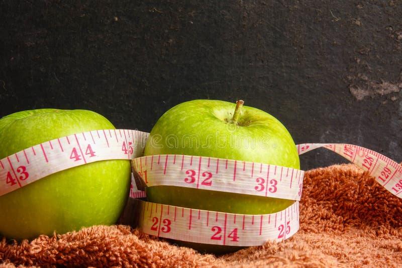 VÅRD- LIVSSTILBEGREPP: Gröna äpplen och mätaband över svart lantlig bakgrund Selektivt fokusera fotografering för bildbyråer