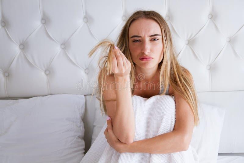 Vård- och skönhet Stående av den härliga ledsna unga kvinnan med långt hår i hand Den olyckliga flickan ligger på säng i sovrum royaltyfri foto
