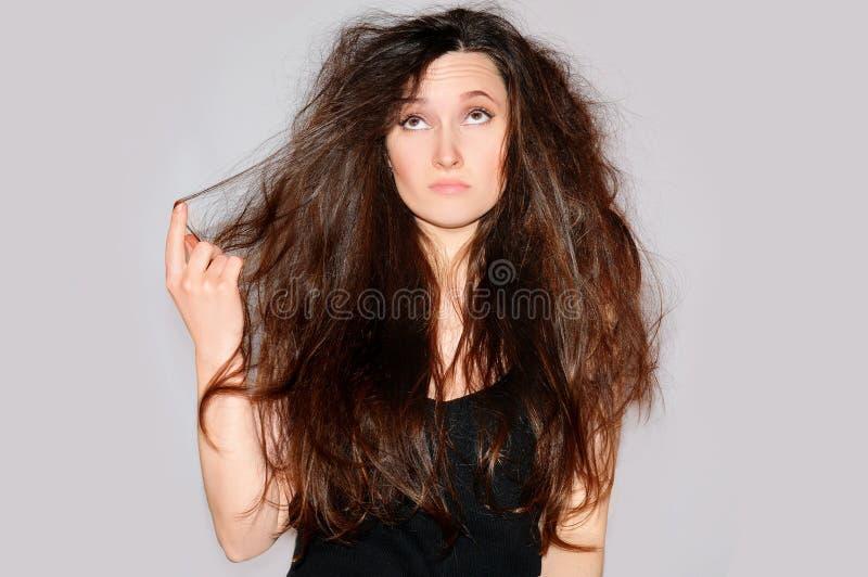 Vård- och skönhet Ung kvinna som ser kluvna hårtoppar Hårspetsar arkivbilder