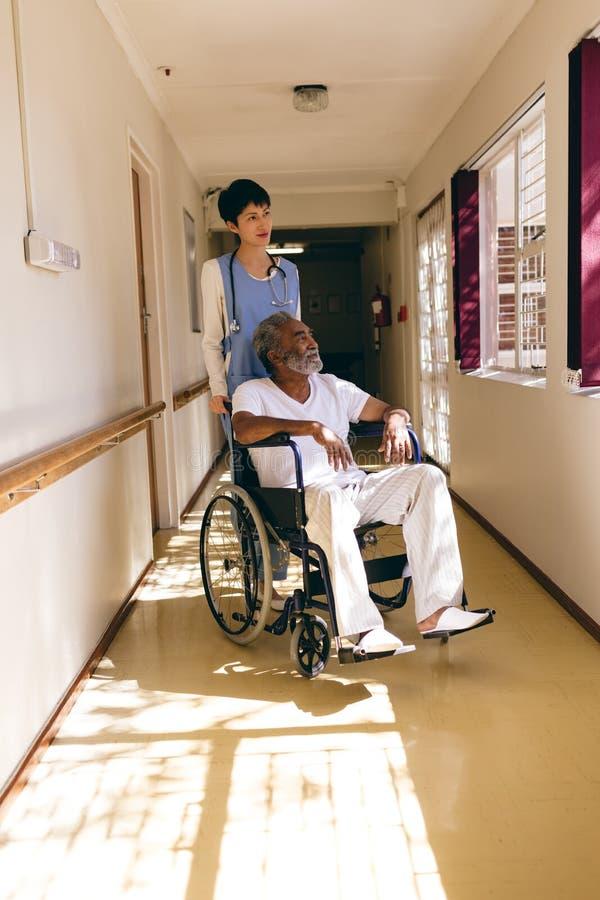 Vårda anseendet, medan mannen sitter i rullstol arkivbild