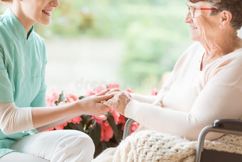 Vårda att förbereda en handikappade personerpensionär för en gå i trädgården av royaltyfri bild