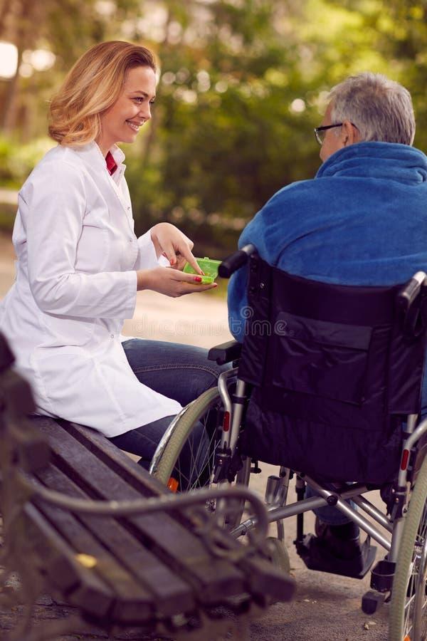 Vårda att ge medicin till den höga mannen i den utomhus- rullstolen arkivfoton