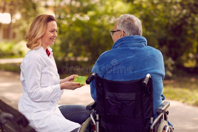 Vårda att ge medicin till den höga mannen i rullstol arkivfoton