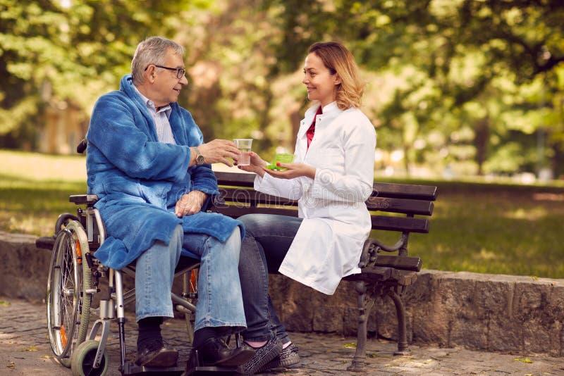 Vårda att ge terapimedicin till den höga mannen i rullstoloutdoo royaltyfri bild