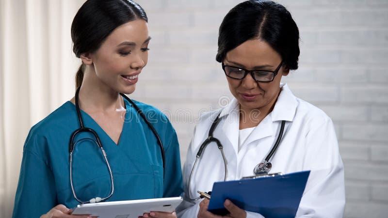 Vårda att kontrollera data i minnestavla och att tala med doktorn som diskuterar diagnos royaltyfria foton
