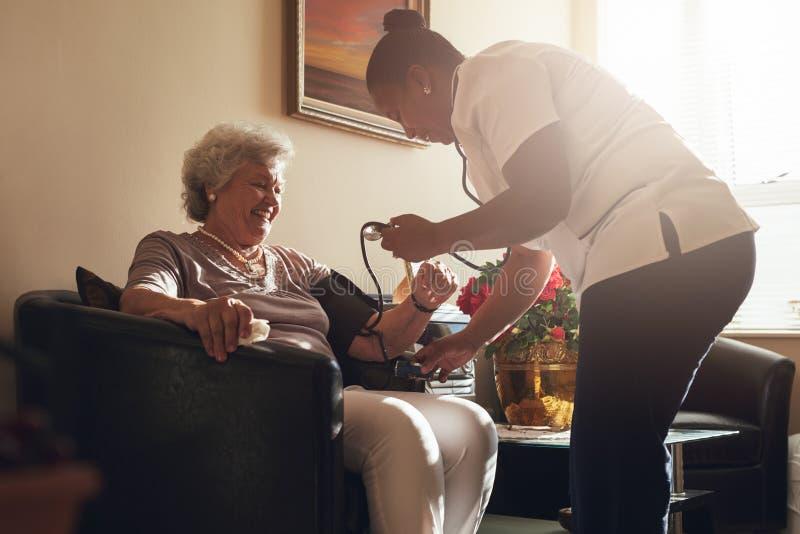 Vårda att mäta blodtryck av den höga patienten i avgångH arkivbild