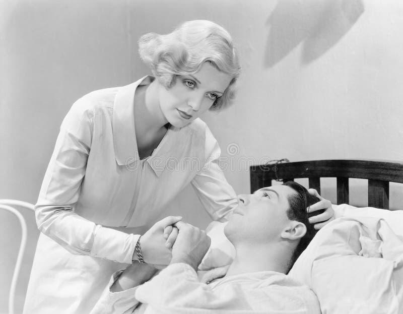 Vårda att trösta en man i en sjukhussäng (alla visade personer inte är längre uppehälle, och inget gods finns Leverantörgarantith fotografering för bildbyråer