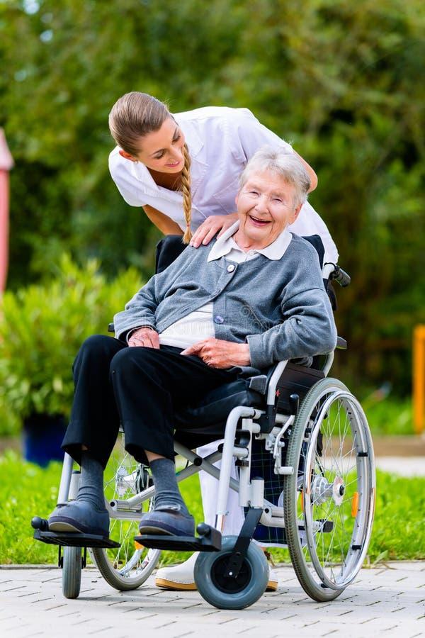 Vårda den driftiga höga kvinnan i rullstol går på arkivbilder