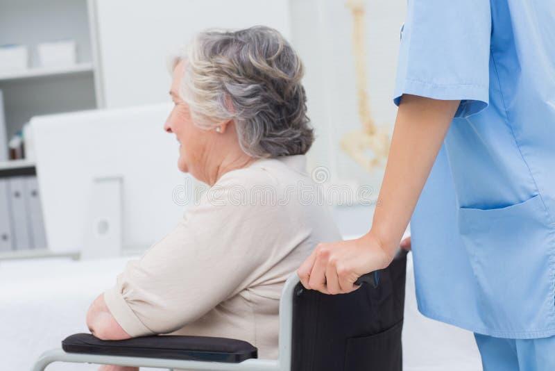 Vårda den driftiga höga patienten i rullstol på kliniken fotografering för bildbyråer