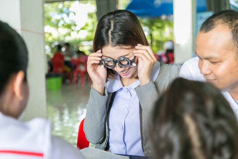 Vårdar det asiatiska barnet att göra visionprovning genom att använda det optiska försöket fr arkivbilder