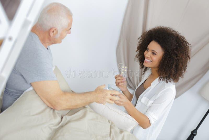 Vårdare som administrerar läkarbehandlingen till patienten royaltyfri foto