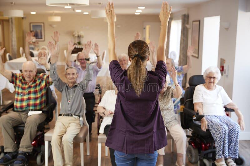 Vårdare som leder gruppen av pensionärer i konditiongrupp i avgånghem royaltyfri foto