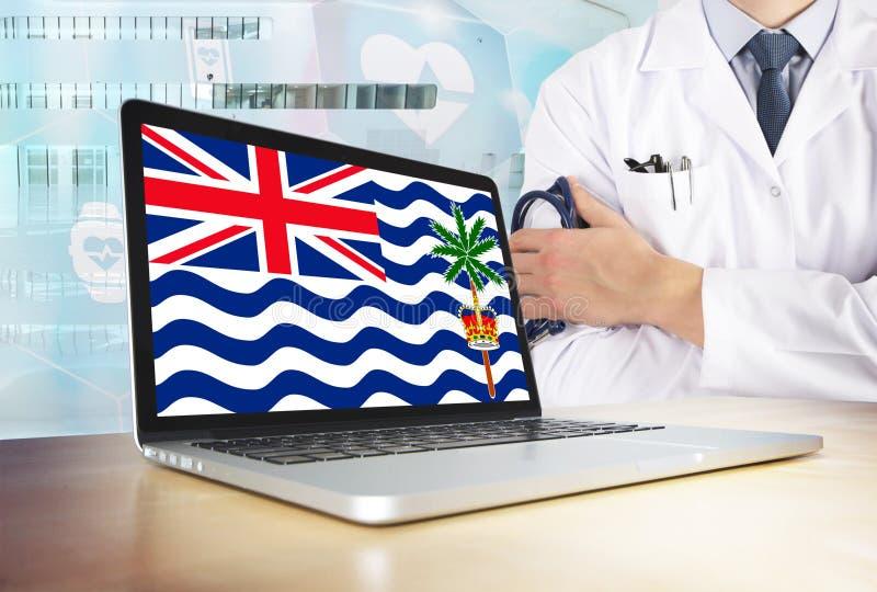 Vårdsystem för brittiskt Indiska oceanenterritorium i techtema Flagga på datorskärmen Doktor som står med stetoskopet in royaltyfri foto