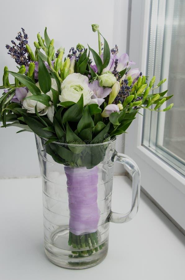 Våren blommar smörblommaranunculusen, lavendel i exponeringsglas på vit bakgrund Ensam fryst tree Svarten boxas med en röd pilbåg arkivfoto