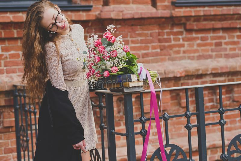 Våren går av en flicka med en blommabukett fotografering för bildbyråer