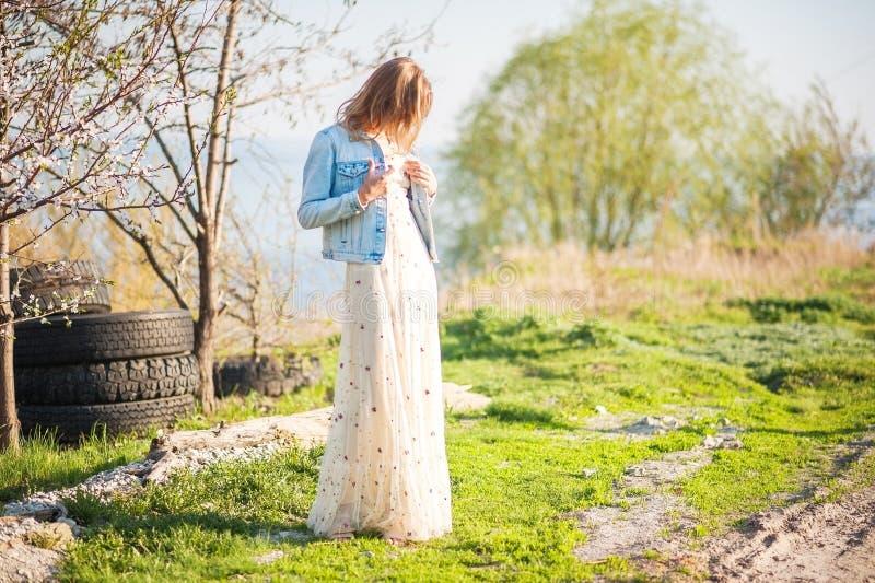 Vårfoto av en härlig ung kvinna på en bakgrund av naturen Flicka i en ljus klänning och ett grov bomullstvillomslag i vår med blo royaltyfri bild