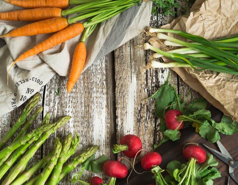 Vårgrönsaker - morötter, rädisor, sparris, salladslökar på en gammal träbakgrund royaltyfri foto