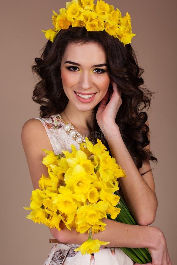 Vårkvinna med buketten av gula blommor arkivbild