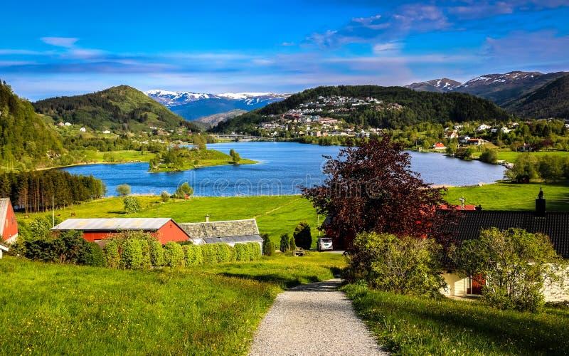 Vårlandskap med överblick av en stillsam dal med gröna ängar, enformad sjö och lantgårdhus i solljuset royaltyfri fotografi