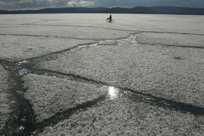 Vårlandskap med isdriva på sjön och en cyklist som rider på den royaltyfri foto