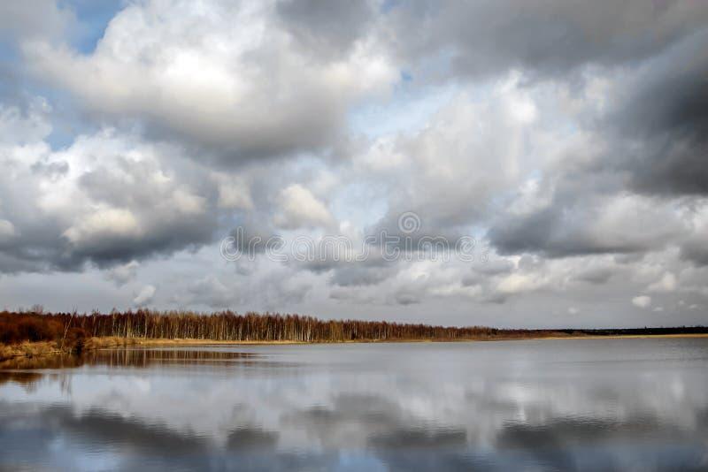 Vårlandskap med sikter av sjön och den molniga himlen royaltyfria foton