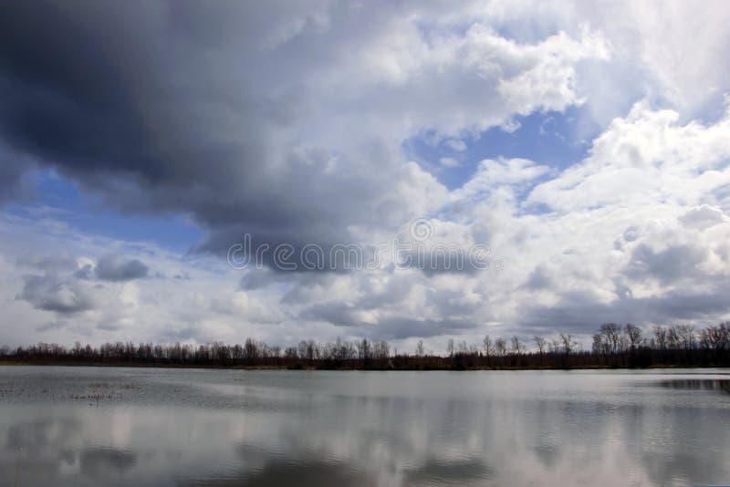 Vårlandskap med sikter av sjön och den molniga himlen royaltyfri fotografi