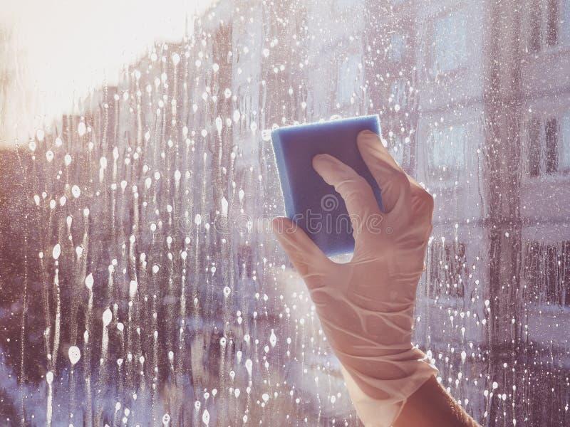Vårlokalvård - lokalvårdfönster Händer för kvinna` s tvättar fönstret som gör ren arkivfoto