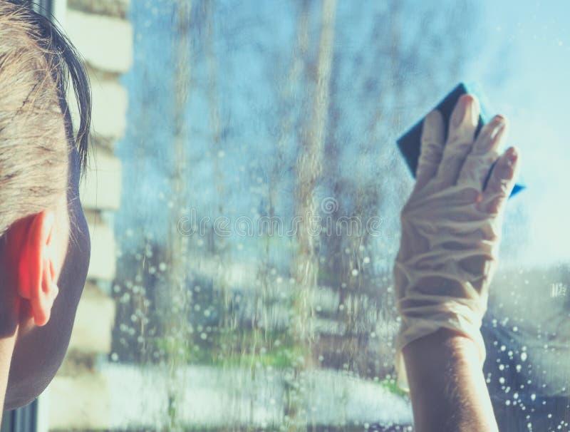 Vårlokalvård - lokalvårdfönster Händer för kvinna` s tvättar fönstret som gör ren fotografering för bildbyråer