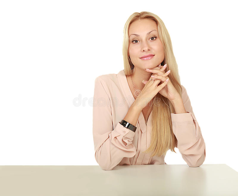 Vårmodell med blomman En ung kvinna med naturligt rent framsidasammanträde på en tabell som lutar på hans armbågar på en vit royaltyfri bild