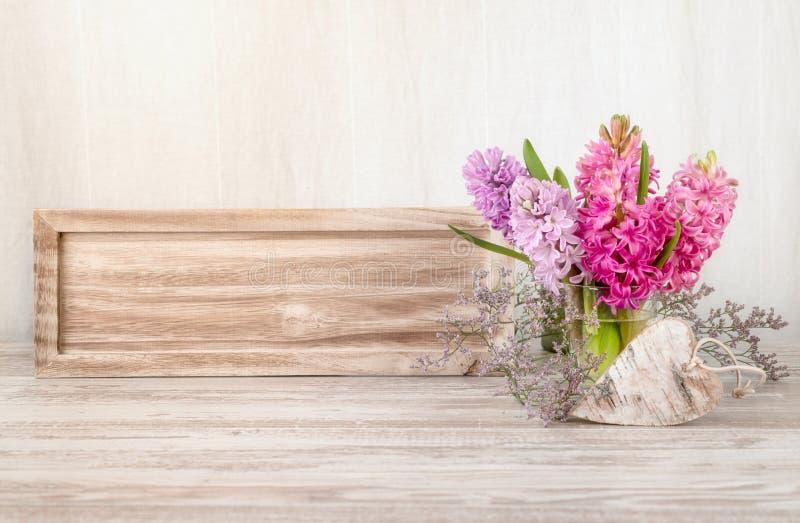 Vårordning med hyacintblommor och trähjärta royaltyfri bild
