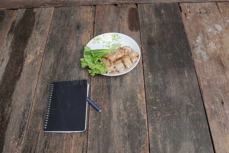 vårrullar häller sås i platta med den svarta anteckningsboken och den nya grönsaken på trätabellen fotografering för bildbyråer