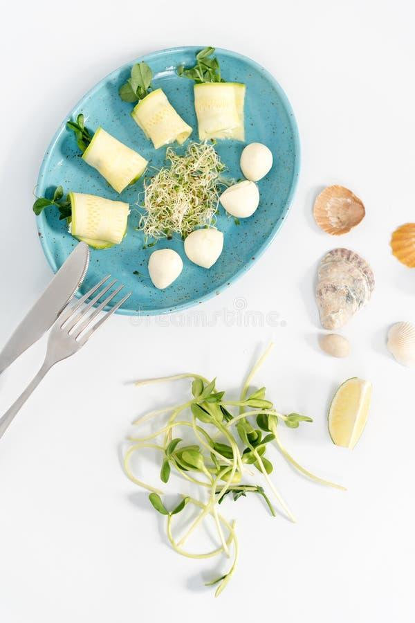 Vårrullar med zucchini- och mozzarellaost Mat med microgräsplaner på vit bakgrund arkivbild