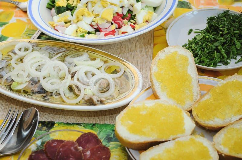 Vårsallad med ägg, gurkor och rädisor, sill med lökar och smörgåsar med pikkaviarställningen på tabellen Användbart och fotografering för bildbyråer