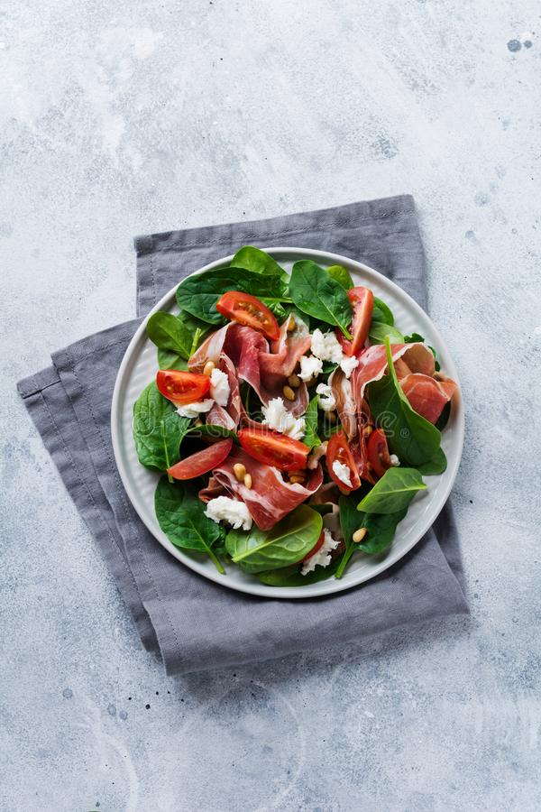Vårsallad med spenat, den körsbärsröda tomaten, mozzarella, sörjer muttrar och skinka med olivolja i en enkel keramisk platta royaltyfri bild