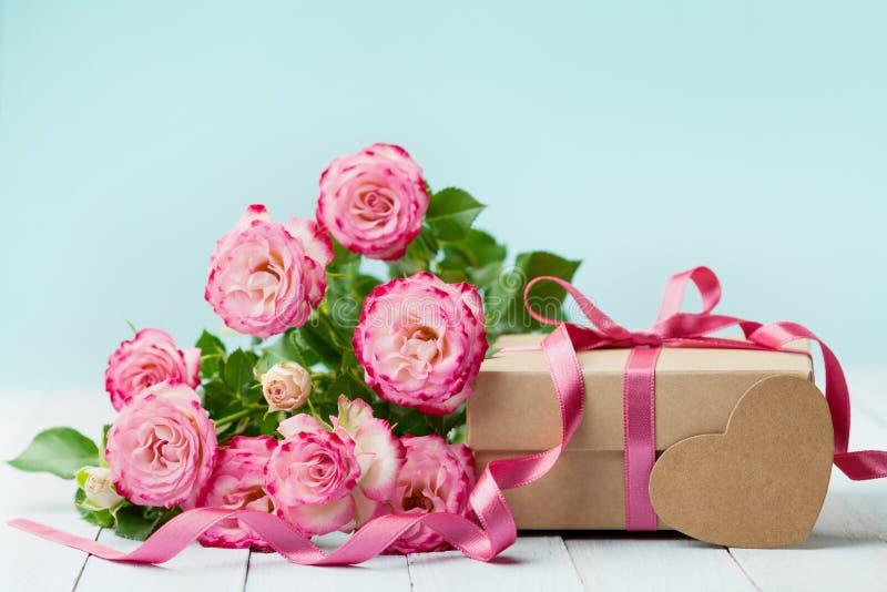Vårsammansättning med rosa färgblommor steg och gåvaasken på tappningtabellen Hälsningkort för födelsedag-, kvinna- eller moderda royaltyfri bild