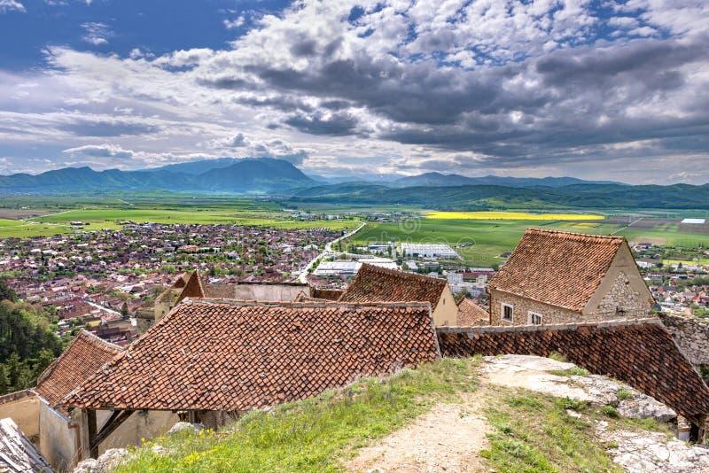 Vårsikt över den Rasnov staden, i det Brasov länet (Rumänien), med gamla hus av den Rasnov citadellen i förgrunden och Piatraen royaltyfria foton