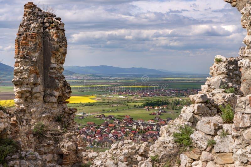 Vårsikt över den Rasnov staden till och med väggarna av den Rasnov citadellen, i det Brasov länet (Rumänien), med det Codlea berg arkivfoton