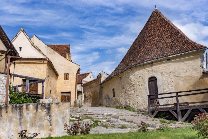 Vårsikt av den inre countryarden för Rasnov citadell, i det Brasov länet (Rumänien), med härliga medeltida stenhus på strömförsör arkivfoton