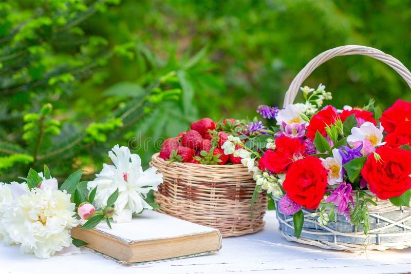 V?rsommarstilleben med en bukett av blommor i en korg, mogna jordgubbar f?r b?r, en gammal bok och vita pioner p? taen arkivfoton