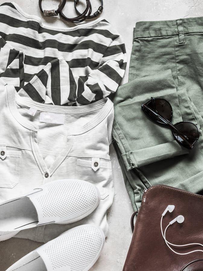 Vårsommaruppsättning av kvinnors tillfälliga kläder - bomullsflåsanden, den vita t-skjortan, randig sweater, piskar gymnastiksko- royaltyfri bild