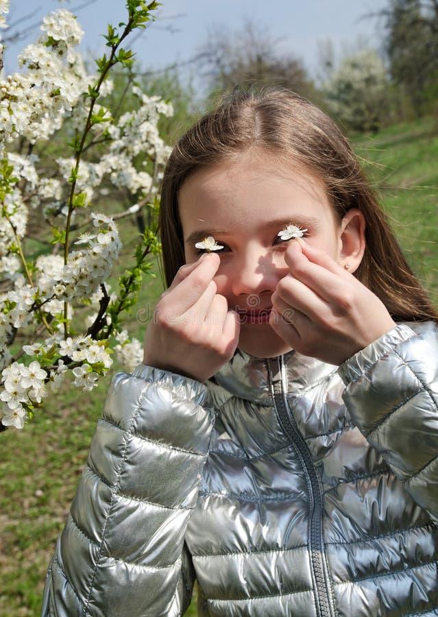 Vårståenden av det gulliga liten flickabarnet har allergin som fjädrar att blomstra royaltyfri fotografi