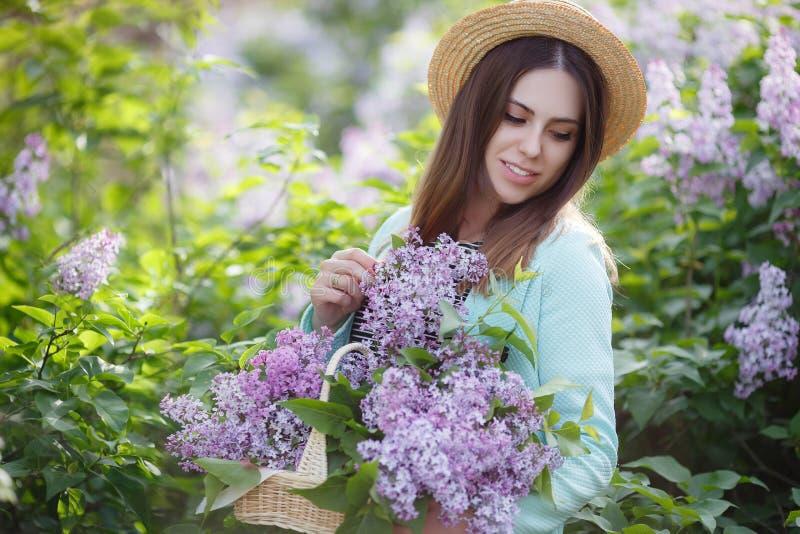 Vårståenden av en härlig kvinna i parkerar utomhus, bland buskarna som blommar lilan royaltyfri fotografi