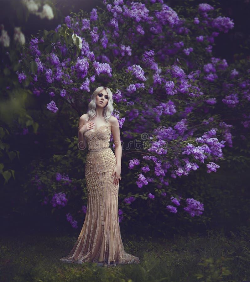 Vårstil Härlig sinnlig flickablondin i vår den blomstra dagträdgården kan spring soligt Ung flicka i en guld- elegant klänning arkivbild