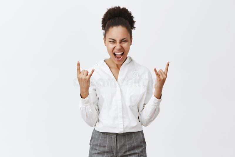 Vårt lag vaggar Upphetsad attraktiv afrikansk amerikan som är kvinnlig med lockigt hår som gör heavy metaltecken och joyfully ler royaltyfri bild