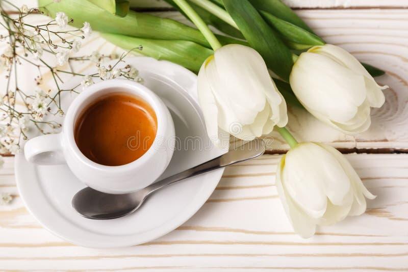 Vårtulpan och kaffe på en vit träbakgrund, bästa sikt Moders bakgrund för dag, kvinnors dag, morgonfödelsedag royaltyfria foton