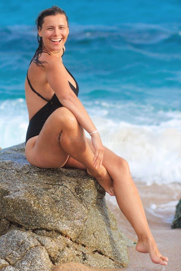 Våt kvinna i baddräkten som sitter på stenen på havet arkivbild