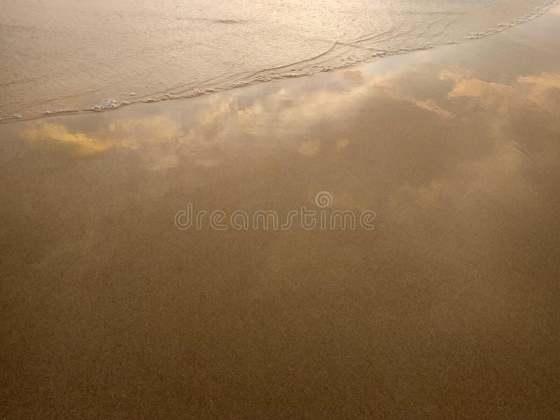 Våt sand med en rasa våg som reflekterar himlen med moln i pastellfärgade färger royaltyfri foto